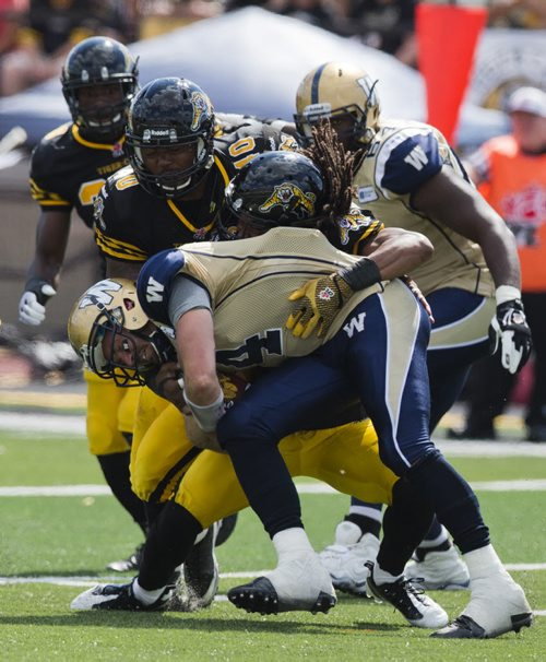 Winnipeg Blue Bombers quarterback Buck Pierce (front) gets sacked by Hamilton Tiger-Cats Rico Murray, as Tiger-Cats Eric Norwood (2nd L) moves to the play during the second half of their CFL football game in Guelph, August 24, 2013.  REUTERS/Mark Blinch (CANADA - Tags: SPORT FOOTBALL) - RTX12VF6