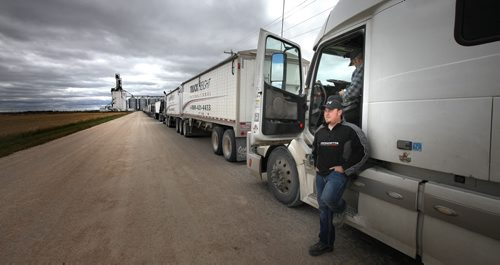 Owner Operator truckers Andy Carr (standing) and Terry Cumberland wait in line at the Patterson Inland Grain Terminal Friday on the NW outskirts of WInnipeg. According to Andy the lineup was about three and a half hours of waiting, they'd been there for about half that time in a line that stretched at least twenty tractor trailers long delivering a record harvest. See Larry Kusch story. September 20, 2013 - (Phil Hossack / Winnipeg Free Press)