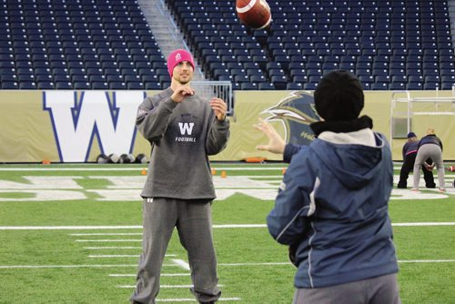 Canstar Community News Quarterback Justin Goltz works on a passing drill with one of the participants in the 2013 Women's Football Clinic. (JORDAN THOMPSON