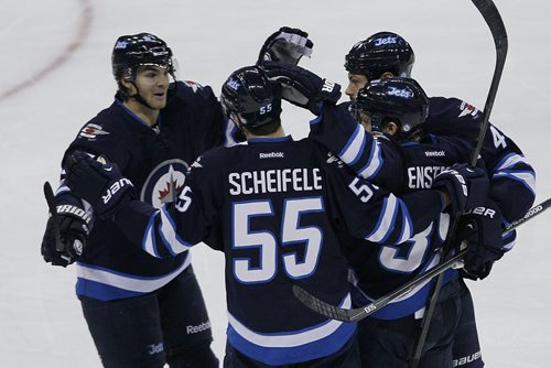 Winnipeg Jets'  Jets' Matt Halishchuk (15), Mark Scheifele (55), Zach Bogosian (44) celebrate a goal by Toby Enstrom (39) against Chicago Blackhawks during first period NHL action in Winnipeg on Saturday, November 2, 2013. THE CANADIAN PRESS/John Woods