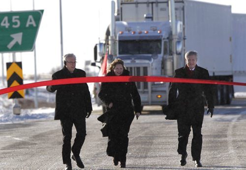 From right, Prime Minister Stephen Harper,Diane Gray, CentrePort's president and CEO and Premier Greg Selinger walk up to their ribbon cutting task to officially open the first section of the new CentrePort Canada Expressway in Winnipeg Friday. CentrePort is the 8,093-hectare inland port and transportation hub being developed northwest of the airport. Wayne Glowacki / Winnipeg Free Press Nov. 22. 2013