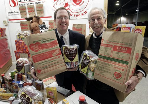 At left, John Graham, with Canada Safeway and Kai Madsen, Executive Director with the Christmas Cheer Board at the launch of the annual Safeway/Christmas Cheer Board grocery bag to collect food for hampers.The bags are distributed by the Winnipeg Free Press and can be filled and dropped off at any Safeway location. Five and ten dollar care packages for hampers can also be purchased at Safeway stores with shoppers collecting a bonus 5 or 10 air miles till Dec.12.    Alex Paul story  Wayne Glowacki / Winnipeg Free Press Nov. 26. 2013