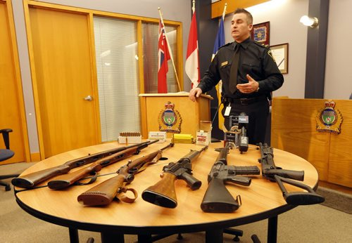 Constable Jason Michalyshen  in pic with guns at  Wpg Police Service Newser , WPS seized drugs and guns from two residences in the 500 block of Chalmers Ave and 3 occupants arrested  and  were taken into custody , a quantity of Meth , Marijuana  hunting and assault weapons were seized in the raid . ** weapons on display were not seized from this arrest , those are still being processed , these represent the kinds of guns found  Dec. 9 2013 / KEN GIGLIOTTI / WINNIPEG FREE PRESS