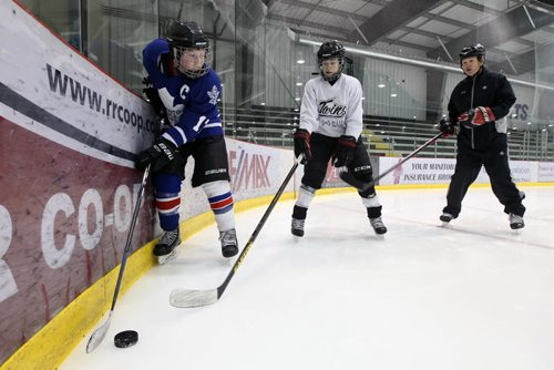 Josh Gardner a  12 A1 hockey player, left,  and  Sean Lett a 13 A hockey player get taught by Hockey Manitoba Master Mentor Hockey Coach Bob Caldwell how to first go for the puck with stick-See Dan Lett 49.8 hockey story – Dec 19, 2013   (JOE BRYKSA / WINNIPEG FREE PRESS)