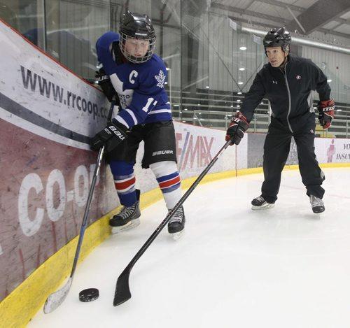 Josh Gardner a  12 A1 hockey player gets taught by Hockey Manitoba Master Mentor Hockey Coach Bob Caldwell how to first go for the puck with stick-See Dan Lett 49.8 hockey story – Dec 19, 2013   (JOE BRYKSA / WINNIPEG FREE PRESS)