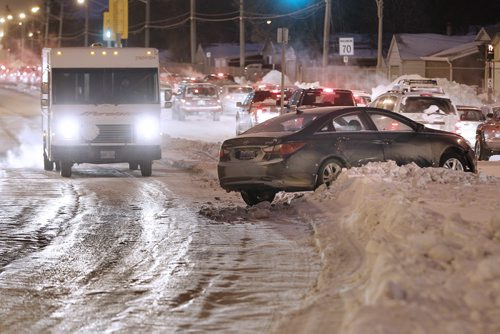 January 6, 2014 - 140106  -  A car ended up on Century Street boulevard after sliding on the icy rut filled road Monday, January 6, 2014. John Woods / Winnipeg Free Press