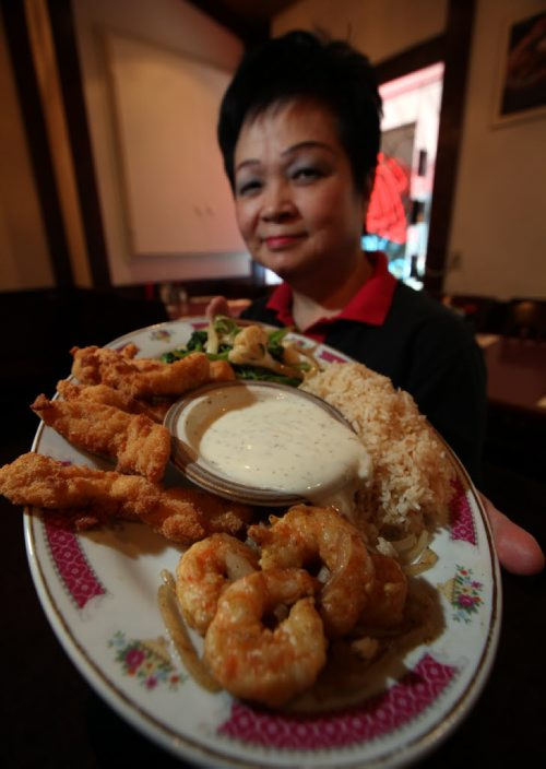 49/8 INTERSECTION - honey dill sauce Shirley Eng holds a platter of shrimp and chicken with her Honey Dill dipping sauce at Mitzi's Chicken Fingers -  What: This is for an Intersection feature on honey dill sauce, a Manitoba-centric dipping sauce that nobody outside the province seems familiar with. Mitzi's has been serving its homemade honey dill sauce for almost 30 years, alongside its world-famous chicken  fingers. So shot of owner Shirley holding up a plate of chicken fingers with a bowl of sauce for dipping... (might be good to get a second shot of the industrial-sized pails of sauce the restaurant stores its honey dill in, 'til they run out & have to slap See story. January 15, 2014 - (Phil Hossack / Winnipeg Free Press)