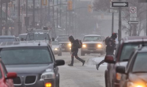 Pedestrians cross Portage Avenue at Fort Street Thursday morning despite the high winds and blowing snow. 140116 - January 16, 2014 MIKE DEAL / WINNIPEG FREE PRESS
