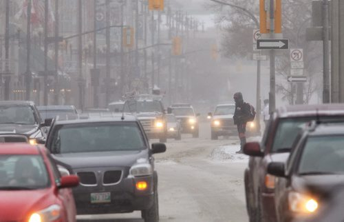 A pedestrian waits to cross Portage Avenue at Fort Street Thursday morning despite the high winds and blowing snow. 140116 - January 16, 2014 MIKE DEAL / WINNIPEG FREE PRESS