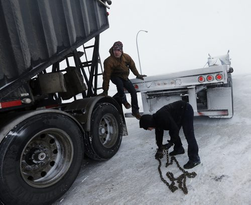 Stdup - Josh Bowland  and (right) Regina Prokopchuk help out fellow trucker  stuck in the parking lot of  truck stop at McGillivray Bld and Perimter Hwy 100 , they pulled the semi  truck out with theirs , they are on their way to Edmonton today Stdup Weather – high winds and blowing snow  are causing white out conditions on the Perimeter Hwy and open area coming into town causing many cars to go off the road  . JAN. 16 2014 / KEN GIGLIOTTI / WINNIPEG FREE PRESS