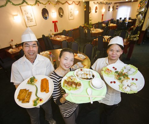 140117 Winnipeg - DAVID LIPNOWSKI / WINNIPEG FREE PRESS (January 17, 2014)  Owner of Kam Ho Chinese Restaurant Teresa Cheng (centre holding hong kong steamed rice roll) with Wai Lee (left, holding turnip cake) and Chao Qiu (right, holding shrimp dumpling)   Restaurant Review - Kam Ho Chinese Restaurant