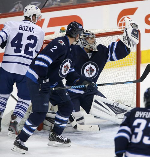 Winnipeg Jets' goaltender Ondrej Pavelec (31) flashes the leather with Toronto Maple Leafs' Tyler Bozak (42) and Jets' Adam Pardy (2) in front of the net during first period NHL hockey action at MTS Centre in Winnipeg, Saturday, January 25, 2014. (TREVOR HAGAN/WINNIPEG FREE PRESS)