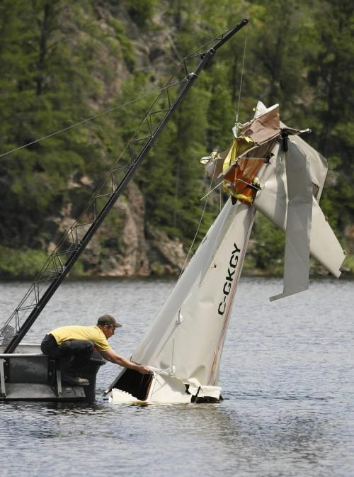 John Woods / Winnipeg Free Press / June 18/07- 070618  - Matt Walker ties a rope to the tail section of a small plane from West Hawk Lake Monday June 18/07.  RCMP removed the plane that crashed in West Hawk Lake Monday June 11/07.  Two men died in the crash.