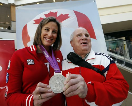 Stdup - Wpg Olympians (left)  Janine Hanson  winner of a silver medal  in women's eight's  rowing 2012  Summer Games in London  showing her medal  at a Polo Park opening of the Red Leaf Lounge at Centre Court , a big screen tv  and stage will be  on hand for customers to watch the Olympics in Sochi Russia  while shopping- (right) 1988 Para Olympian Shep Shell , blind marathon runner was also  on hand to meet the public on this, the opening of the 2014 Olympics , FEB. 7 2014 / KEN GIGLIOTTI / WINNIPEG FREE PRESSFEB. 7 2014 / KEN GIGLIOTTI / WINNIPEG FREE PRESS