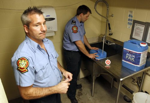 Update on City services relating to frozen water pipes. Winnipeg Fire Paramedic Service preparing water jugs for delivery at Winnipeg Fire and Paramedic Station 22, 1567 Waverley Street. In this photo Jay Simons and Dale Worrall demo on how they are gonna clean and fill the water jugs. BORIS MINKEVICH / WINNIPEG FREE PRESS  March 7, 2014