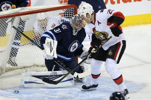 Winnipeg Jets' goaltender Ondrej Pavelec (31) and Ottawa Senators' Chris Neil (25) watch the puck slide through the crease during first period NHL hockey action at MTS Centre in Winnipeg, Saturday, March 8, 2014. (TREVOR HAGAN/WINNIPEG FREE PRESS)