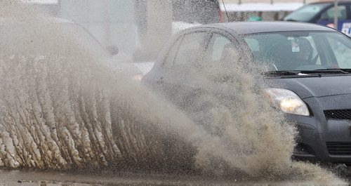 The wet season is just around the corner for those of you sick of the snow… cars send up large sprays of water as they travel along Portage Avenue Monday afternoon.   140317 - March 17, 2014 MIKE DEAL / WINNIPEG FREE PRESS