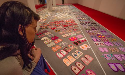 Erin Konsmo, the national collective youth coordinator and media contact for the Walking With Our Sisters commemorative art installation project, spends time with the installation at the Urban Shaman Gallery in Winnipeg on Friday, March 21, 2014. The project seeks to honour to the lives of missing and murdered Indigenous women and girls by displaying over 1760 donated moccasin tops, or vamps, each of which are intentionally not sewn into moccasins, and represent the unfinished lives of Indigenous missing and murdered women and girls. The project is currently booked to tour more than 30 locations across North America over the next six years, into the year 2019. (Photo by Crystal Schick/Winnipeg Free Press)