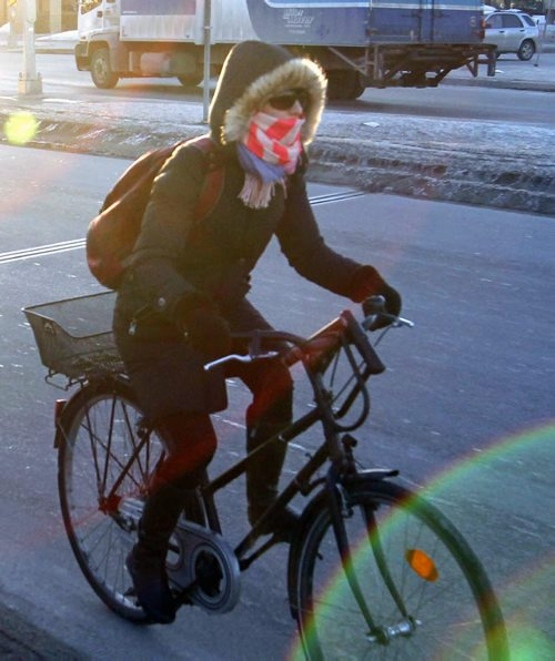 A cyclist is dressed for the -16C temperature Friday morning while travelling over the Esplanade Riel .   For weather story.  Wayne Glowacki / Winnipeg Free Press March 28   2014