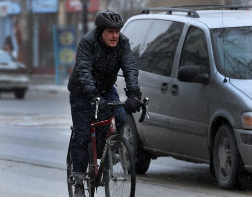 STDUP – Snow Will Fall . Snow is beginning to fall in downtown Winnipeg . Cyclist on Portage Ave. contends with light snow . April 3 2014 / KEN GIGLIOTTI / WINNIPEG FREE PRESS