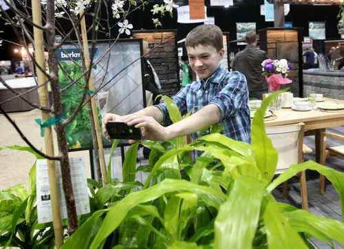 Twelve year old Matthew Trudeau takes pictures of a plant display at the Home Expression Show at the Convention Centre Saturday in hopes of planting a garden with his mom this spring.  Standup photo  April 05,  2014 Ruth Bonneville / Winnipeg Free Press