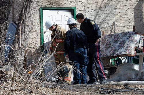 A fire official and police officers examine the door of a home on the 300 block of Enfield Crescent near Marion Street.  The basement resident died as a result of the fire.  The cause of the early morning fire is under investigation.  EMILY CUMMING / WINNIPEG FREE PRESS APRIL 16, 2014