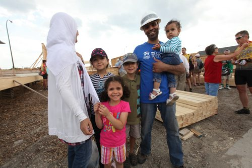Cycle of Hope raised $170,000 dollars for a  Habitat home that this family will be moving into.  Photo of the family that will be moving into the home that the Cycle for Hope members raised money for. Mohamed (dad) holds 16 month old Rahaf,  Rami in grey hat (8), Ranin in purple hat (10), Rawan in her pink shirt (6) with their mother on far left. Note: The last name of family is not provided to the media due to safety issues.  The mother chose not to use her first name or have her full face on camera.   See Ashley Prest Story.  July 12, 2014 Ruth Bonneville / Winnipeg Free Press