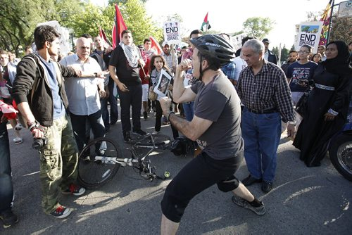 "July 14, 2014 - 140714  -  An Israel supporter provokes peaceful Palestinian supporters by yelling ""stop hiding behind your children"" as they hold a rally at the Manitoba Legislature Monday, July 14, 2014. John Woods / Winnipeg Free Press"