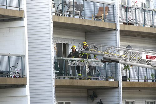 Residents were evacuated from the Adsum Square Apartments on Adsum Drive Friday after a possible lightning strike to the building.Fire Fighters on a second floor balcony.   Wayne Glowacki/Winnipeg Free Press August 8 2014