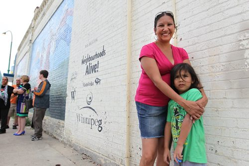 Althea Guiboche, also known as the Bannock Lady, stands near the corner where she hands out free bannock  weekly (Dufferin & Main) with her children after talking to the media about her views on the recent Facebook posting scandal.  WIth her son Justin (6yrs). See story.   Aug 09, 2014 Ruth Bonneville / Winnipeg Free Press