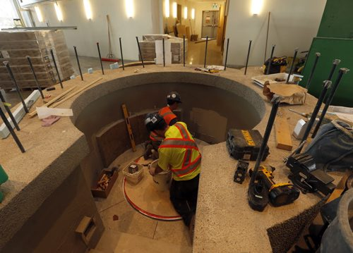 FAITH . Rev. Darren Gurr  at his new parish church St. Gianna  Beretta Molla  Roman catholic Church still under construction  , a brand new $14 million Roman catholic Church  on Columbia that features  circular  worship area with alter in the centre of the space ,in pic  workers  finishing area for glass bottomed baptismal in the  modern architecture  church . Aug 12 2014 / KEN GIGLIOTTI / WINNIPEG FREE PRESS