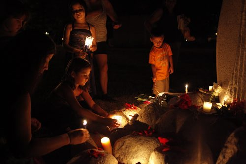 August 19, 2014 - 140819  -  People place candles at the base of a monument for murdered and missing women after a vigil and walk for homicide victim fifteen year year old Tina Fontaine and Homeless Hero Faron Hall who were pulled from the Red River Sunday takes place Tuesday, August 19, 2014. . John Woods / Winnipeg Free Press