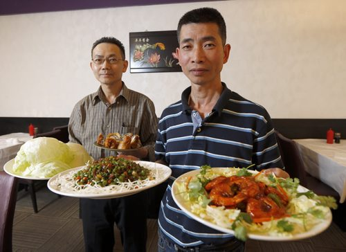 REST REVIEW - SAM PO for Review . SAM PO RESTAURANT 277 Rupert Ave.- LtoR  Mgr. Wai Ng holding Brazed prawns in Tomato Sauce, with owner  Wu Yu  holding  speciality dishes Diced duck,   & Lobster Roll . SEPT  29 2014 / KEN GIGLIOTTI / WINNIPEG FREE PRESS