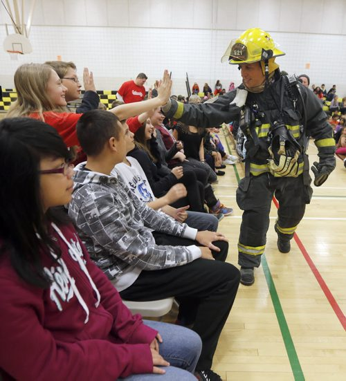 STDUP . Fire Prevention Week starts Oct 5 to11  . WFS firefighter Marcel Laporte give high fives to students at the assembly .The  to  the pubic is reminded to check their smoke alarm and carbon monoxide detector batteries as well a review  home escape plans in case of fire .This years  kick off was held at Bernie Wolfe School other activities during the week include WFS Fire Drill across the city schools on Friday  and Saturday  the Fire paramedic stations are open to the public for tours as well as Fire Chief for a Day event . Oct. 6 2014 / KEN GIGLIOTTI / WINNIPEG FREE PRESS