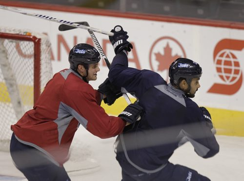 At left, Winnipeg Jets #2 defenceman Adam Pardy sticks close to winger Dustin Byfuglien  at the team practice in the MTS Centre Thursday. Tim Campbell  Story.Wayne Glowacki / Winnipeg Free Press Oct.16 2014
