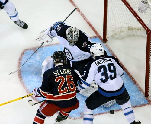 Winnipeg Jets' goaltender Ondrej Pavelec (31) stops the puck with New York Rangers' Martin St. Louis (26) and Tobias Enstrom (39) in front of the net during second period NHL hockey at Madison Square Garden in New York City, Saturday, November 1, 2014. (TREVOR HAGAN/WINNIPEG FREE PRESS)