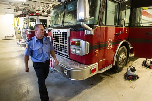 A fire paramedic walks by a truck after returning from a call during a tour of the new Winnipeg Fire Paramedic Service Station 11 at Portage Avenue and Route 90. 141211 - Thursday, December 11, 2014 -  (MIKE DEAL / WINNIPEG FREE PRESS)