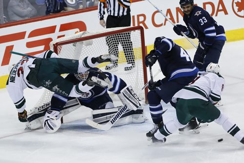 Minnesota Wild's Nino Niederreiter (22) flies across the crease of Winnipeg Jets goaltender Michael Hutchinson (34) as Jets' Zach Bogosian (44) and Wild's Mikko Koivu (9) look for the rebound and Jets' Dustin Byfuglien (33) looks on during first period NHL action in Winnipeg on Tuesday, February 10, 2015. (John Woods / WINNIPEG FREE PRESS)