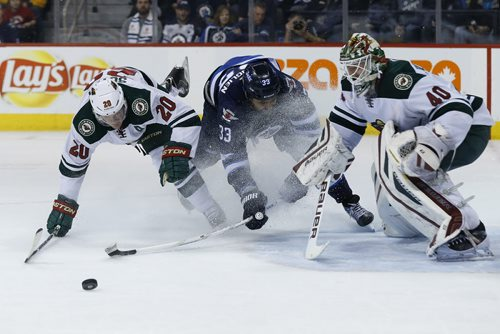 Winnipeg Jets' Dustin Byfuglien (33) draws a holding penalty on Minnesota Wild's Ryan Suter (20) as he was driving for the loose puck in front of Wild goaltender Devan Dubnyk (40) during second period NHL action in Winnipeg on Tuesday, February 10, 2015. (John Woods / WINNIPEG FREE PRESS)