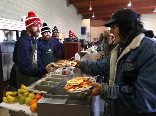 From left, Winnipeg Goldeyes pitchers Nick Hernandez and Coby Cowgill  help out serving a hearty breakfast at Agape Table Monday morning to guests including Bruce Jamieson. This is the second year the Goldeyes team have helped to volunteer with a breakfast and they also passed out free tickets to ball games.   Wayne Glowacki / Winnipeg Free Press May 11  2015