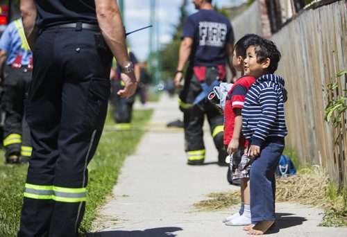 Children are evacuated from a fire at a day home at 703 Burrows Avenue in Winnipeg on Thursday, June 18, 2015.  Nobody appeared to be injured. Mikaela MacKenzie / Winnipeg Free Press