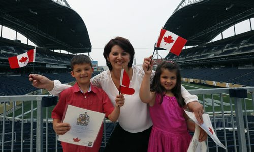 Hysnije Krasnigi with her children Dion,7, at left and Dea,5, originally from Kosovo were among the 100 people that became Canadians at the Citizenship Ceremony in the Pinnacle Club at Investors Group Field Monday. The new Canadians were treated to tickets for the Winnipeg Blue Bombers Home Opener on July 2nd  and will  be honoured at the  special half-time presentation with the citizens at centre field. ¤  see release .Wayne Glowacki / Winnipeg Free Press June 29  2015