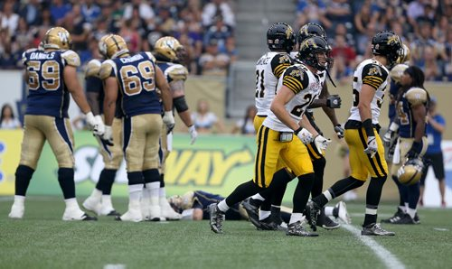 The Hamilton Tiger-Cats'  celebrate and the Winnipeg Blue Bombers' look on with concern after Taylor Reed (44) and Adrian Tracy (93) sacked Winnipeg Blue Bombers' quarterback Drew Willy (5). Willy would be hurt on the play and be forced to leave the game. Thursday, July 2, 2015. (TREVOR HAGAN/WINNIPEG FREE PRESS)