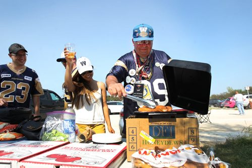 Tail Gating- Jennifer Downing and John Couture prepare some hotdogs in parking lot outside Investors Group Field Friday before the game between the Montreal Alouettes and the Winnipeg Blue Bombers- –Standup Photo- July 10, 2015   (JOE BRYKSA / WINNIPEG FREE PRESS)