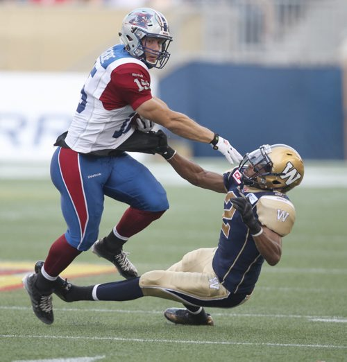 Winnipeg Blue Bomber Matt Bucknor  trys to grab Montreal Alouettes  Samuel Gigure during first half CFL action in Winnipeg Friday night- -See Paul Wiecek story- July 10, 2015   (JOE BRYKSA / WINNIPEG FREE PRESS)