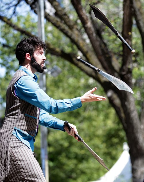 "Catch That Act...Michael Armstrong, or on stage aka ""Mr Wizowski"" juggles knives for the crowd's entertainment Wednesday afternoon at the Fringe Festival's free stage in Old MArket Square. July 22, 2015 - (Phil Hossack / Winnipeg Free Press)"