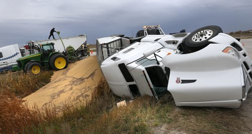 Workers retrieve the grain from an overturned semi-trailer that blocked one of the northbound lanes of Highway 7 just north of the Perimeter Highway at Road 69 Wednesday afternoon. The uninjured driver was out helping with the cleanup.   Wayne Glowacki / Winnipeg Free Press October 7 2015