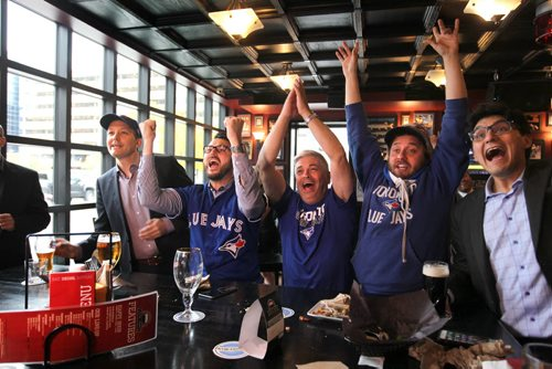 Toronto Blue Jays baseball fans celebrate after the Jays got a run in the 6th inning as they watch the game against Texas on TV at the Pint Thursday afternoon.   Names from left - Ross McFadyen (hat, suit jacket), Scott Hoeppner (glasses, jersey), Glen Agar (white hair, centre), Chris Stanton (hat, jersey, cape) and Sacha Paul (suit, far right). Oct 08, 2015 Ruth Bonneville / Winnipeg Free Press