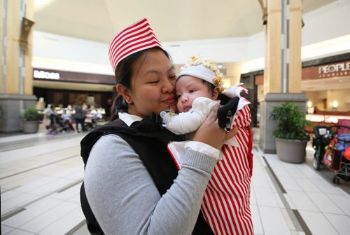 Aileen Linsingan holds her 2 month old son, Brayden in her arms dressed who is dressed as a bag of popcorn with her as the vendor, a costume she made after seeing it on Pinterest, while at Kildonan Place mall with her kids Friday afternoon for their annual Trick or treating at the mall event.   Standup photo Oct 29, 2015 Ruth Bonneville / Winnipeg Free Press
