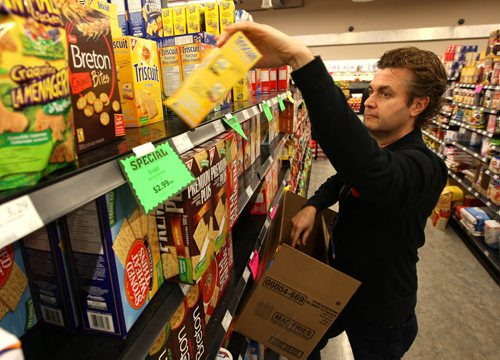 "Cantor's Quality Meats and Groceries owner Ed Cantor loads up some groceries into a box for delivery. It's for a story on the growth of online grocery shopping. Cantor's is one of a handful of local independent grocery stores which not only offer online grocery shopping, but also  deliver the groceries. A number of big players, like Walmart and Loblaw, are experimenting with offering a compromise ""click and collect"" service, where customers can order online but have to pick up their order at the store of their choice. BORIS MINKEVICH / WINNIPEG FREE PRESS  NOV 3, 2015"